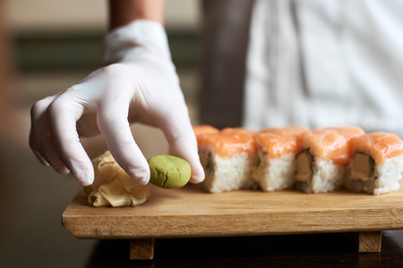 Close-up view of process of preparing delicious rolling sushi. Masters hand is holding wasabi