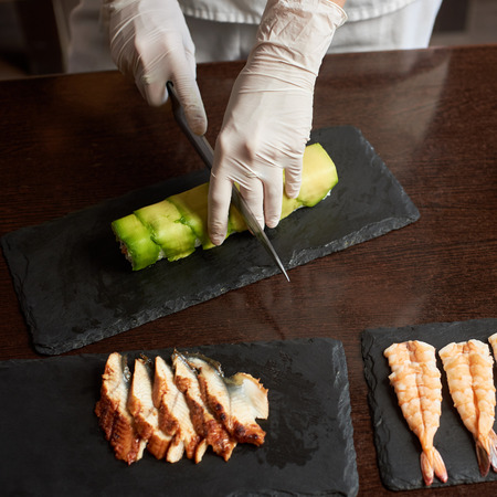 Closeup view of process of preparing rolling sushi. hands in gloves cutting roll on the black stone plate