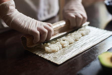 Closeup view of process of preparing rolling sushi. Master making a sushi roll with bamboo mat.