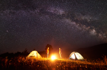 Night camping. Bright campfire burning between two hikers, man and woman standing opposite each other in front of shining tents under amazing dark starry sky with Milky way on distant hills background