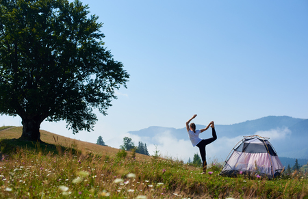 Back view of young slim girl in white T-shirt standing on one leg in yoga pose on green grassy hill at tourist tent under beautiful blue sky on foggy mountains background. Tourism and camping concept. Banco de Imagens