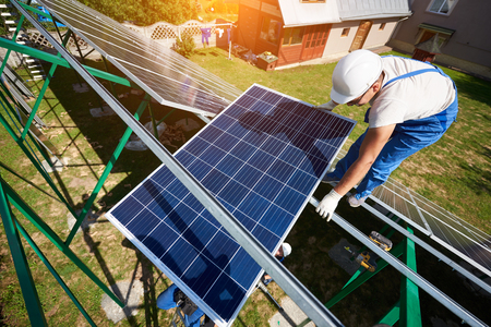 Mounter installing solar panels on green carcass. Innovative solution for electricity saving, using renewable energy of sun. High-tech exterior, modern equipment, ecological friendly, green energy. Stock Photo