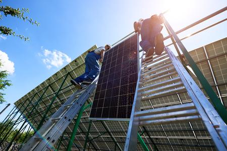 Équipe de travailleurs professionnels installant des panneaux solaires sur la construction métallique verte à l'aide de différents équipements. Solution innovante pour la résolution d'énergie. Utilisez des ressources renouvelables. Énergie verte.