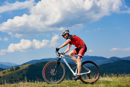 Athlete sportsman bicyclist in professional sportswear and helmet riding cross country bicycle on summer day. Mountains view and cloudy sky on background. Active lifestyle and outdoor sport concept 免版税图像