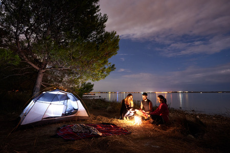 Group of three tourists, young man and women sitting on lake shore at bonfire near tourist tent under tree. Quiet water surface and evening sky on background. Tourism, friendship and camping concept.
