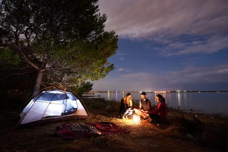 Groupe de trois touristes, jeune homme et femmes assis sur la rive du lac au feu de joie près de la tente touristique sous l'arbre. Surface de l'eau calme et ciel du soir sur fond. Concept de tourisme, d'amitié et de camping.