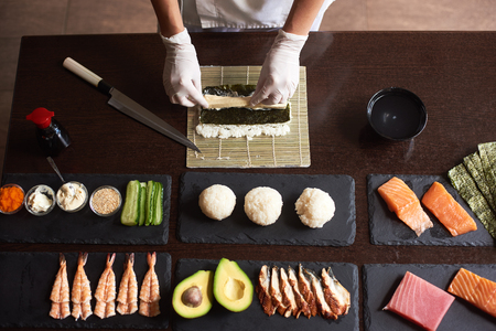 Close-up viev of chef hands preparing japanese food. Chef making sushi rolls at restaurant with many ingredients on the black stone plates. View from the top