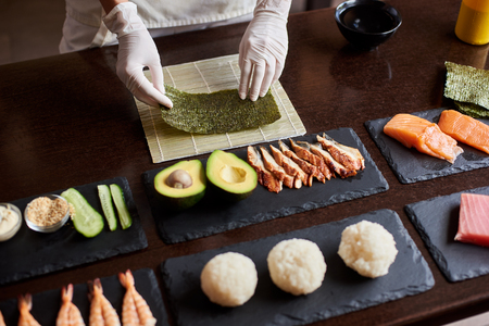 Close-up view of process of preparing rolling sushi. Chefs hands are holding sheet of nori. Ingredients: cucumber, salmon, rice, avocado on black stone plates 写真素材