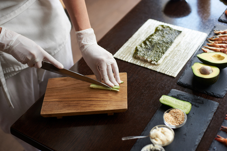 Close-up view of process of preparing delicious rolling sushi in restaurant. Female hands in disposable gloves slicing cucumber on wooden board.