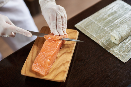 Close-up view of process of preparing delicious rolling sushi in restaurant. Female hands in disposable gloves slicing salmon on wooden board.