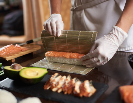 Close up view of process of preparing rolling sushi with disposable gloves on bamboo mat Banco de Imagens