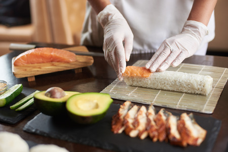 Closeup viev of chef hands preparing japanese food. Chef making sushi rolls at restaurant with many ingredients on the black stone plates. Banco de Imagens