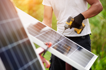 Technician worker assembling shiny solar photo voltaic panels using electrical screwdriver standing outdoors on bright green sunny colorful blurred bokeh background. Efficiency and professionalism.