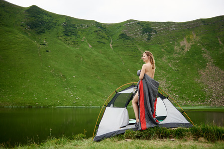 Side view of beautiful female tourist standing in tent entrance in sleeping bag, beautiful view of lake in the mountains on the background. Camping lifestyle concept adventure summer vacations outdoor