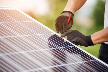 Nahaufnahme-Techniker Hände in Schutzhandschuhen, die Markierung mit Bleistift auf Metallplattform für die Installation des Solar-Foto-Voltaik-Panels auf unscharfem grünem Sommerhintergrund machen.