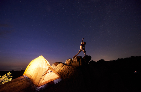 Camping site in mountains. Bright tourist tent on steep rock and young slim woman posing with raised arm on dark blue starry evening sky. Tourism, yoga, active lifestyle, climbing concept.