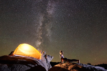 Athletic girl doing push-up exercises on big boulder on night starry sky with Milky way and brightly lit tourist tent background. Active lifestyle and mountain camping concept. Urdhva Mukha Shvanasana Archivio Fotografico