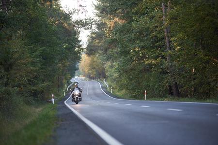 Bearded bikert riding modern powerful high-speed motorcycle along asphalt road winding among tall green trees. Stock Photo