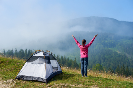 Back view of active tourist girl standing with raised arms on hill at tourist tent, enjoying foggy mountains view on bright summer sunny morning. Tourism and traveling concept. Carpathian mountains Stock Photo