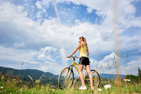 Back view of attractive happy female cyclist standing with yellow mountain bike, enjoying summer day in the mountains. Outdoor sport activity, lifestyle concept