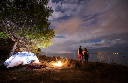 Back view of young tourist couple, athletic man and slim woman standing embraced near tourist tent by campfire on evening sky and sea water background. Active lifestyle and loving relations concept. Stok Fotoğraf