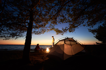 Camping on sea shore at night. Tourist tent under trees and young family, man and woman preparing food gas burner near campfire on blue evening sky and water background. Tourism and adventure concept.