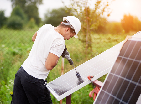 Profile of professional worker in helmet connecting solar photo voltaic panel to metal platform using electrical screwdriver outdoors on bright sunny day on blurred green rural landscape background.