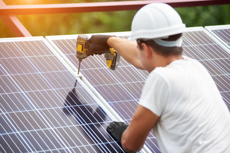 Back view of young technician in helmet connecting solar photo voltaic panel to metal platform using electrical screwdriver on shiny surface background. Stand-alone solar panel system installation.