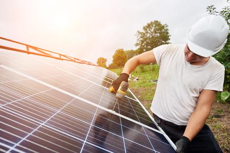 Professionele technicus die werkt met een schroevendraaier die zonne-fotovoltaïsche paneel verbindt met het metalen exterieurplatform onder heldere blauwe hemel. Alternatieve hernieuwbare ecologische groene energieconcept. Stockfoto