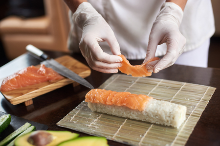 Close-up view of process of preparing rolling sushi with disposable gloves on bamboo mat
