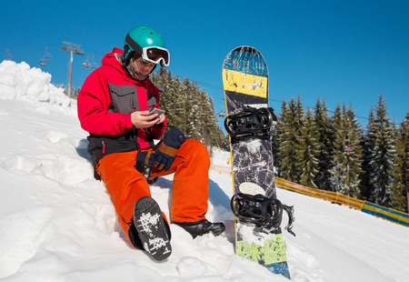 Snowboarder sitting in the snow at ski resort,using his smart phone while resting in the mountains technology communication carrier mobility recreation sport lifestyle 版權商用圖片