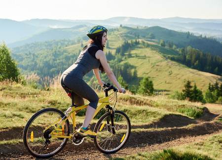 Attractive smiling woman biker riding on yellow bicycle on rural trail in the mountains, wearing helmet, on summer day. Mountains, forests on the background. Outdoor sport activity, lifestyle concept