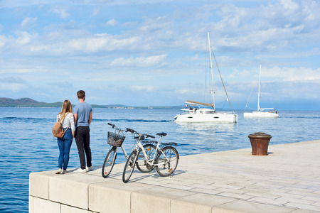 Back view of tourist couple, man and woman with backpack standing at bicycles on high paved stone sidewalk watching floating cruise yachts in clear blue sea water on sunny day. Active holiday concept. Banco de Imagens