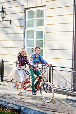 Young active smiling traveler couple, handsome bearded man and pretty blond woman in glasses riding together tandem bicycle along paved sidewalk on bright sunny autumn day by ancient buildings.