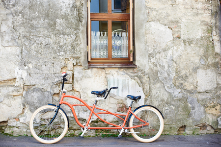 Modern comfortable orange tandem double bicycle with white wheels leaned to the old plastered cracked vintage house wall with lace curtain on small clean window on bright sunny summer day. 免版税图像