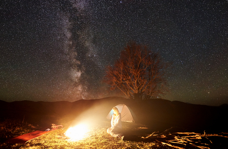 Camping night in mountains. Woman tourist resting near burning campfire under starry sky and Milky way. Illuminated tent and silhouette of big tree in background. Tourism and outdoor activity concept
