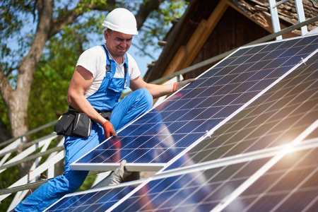 Professional technician adjusting heavy solar photo voltaic panel to high metal platform on blue sky and green tree background. Stand-alone solar system installation, green energy production concept.