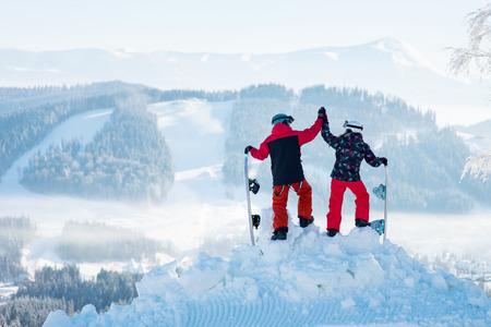 Shot of a couple high fiving each other posing on top of a snowy mountain observing stunning winter view resting after snowboarding extreme people romantic friendship trip getaway. Stock fotó