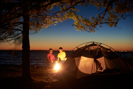 Night camping at sea. Tourist tent under tree and young couple, man and woman at campfire against evening sky and orange glow on horizon. Tourism, happy relations and active lifestyle concept.