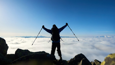 Back view of tourist hiker in winner posture on big boulders with trekking poles in raised arms on bright blue sky at dawn, foggy valley filled with white clouds and mountain tops background.