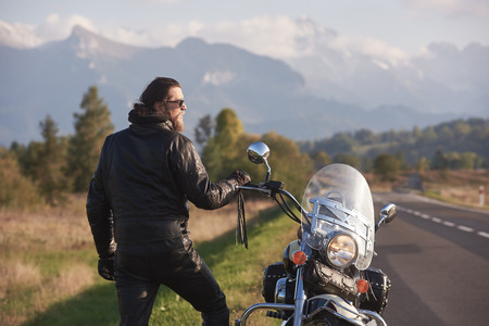 Bearded athletic motorcyclist in dark sunglasses, black leather clothing standing at modern cruiser motorbike on background of green rural landscape, steep mountain peaks. Фото со стока