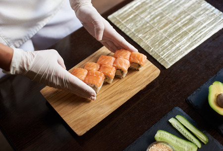 Close-up view of process of preparing rolling sushi. Chef is serving fresh delicious rolls on the wooden board