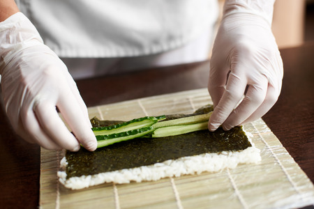 Close-up view of process of preparing rolling sushi. Nori, white rice and cucumber on bamboo mat. Chefs hands in gloves starts cooking sushi rolls