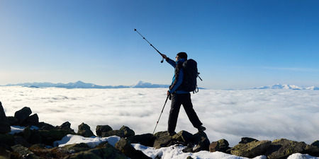 Tourist hiker with backpack standing on huge rocks pointing with trekking pole at bright blue sky on background of foggy valley filled with white clouds and distant mountain tops.