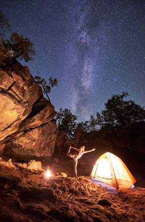 Campsite at night amid huge steep mountain rock formations. Attractive young woman doing yoga exercises at tourist tent on clear dark blue starry sky background. Tourism and sport concept. Narajasana Archivio Fotografico