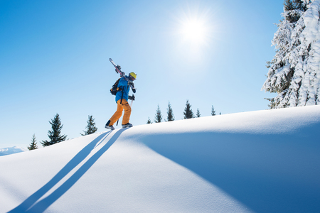 Low angle shot of a skier walking on top of the mountain with his skis on his shoulder on a sunny winter day sunlight nature recreation skiing lifestyle downhill sportive concept.