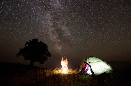 Camping night in mountains. Young hiker woman sitting in entrance of illuminated tent, enjoying brightly burning bonfire under beautiful deep dark starry sky and Milky way. Tourism and travel concept