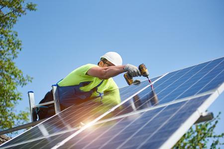 Technicus die fotovoltaïsch zonnepaneel verbindt met metalen platform met behulp van een schroevendraaier die op een ladder staat op een heldere blauwe hemelkopieerruimteachtergrond. Stand-alone installatieconcept voor zonnepanelen.