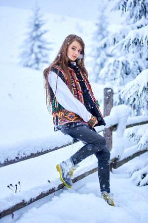 Young attractive fashionable long-haired woman in jeans, white traditional Ukrainian embroidered blouse and multicolored woolen vest at simple wooden fence outdoors on winter blurred background. Stock Photo