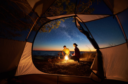 Camping on sea shore at sunset, view from inside tourist tent. Young tourist couple, man and woman preparing food on gas burner, sitting near campfire on blue sea water and starry sky background
